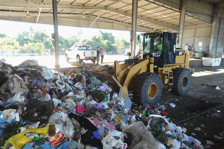 A bulldozer collects waste