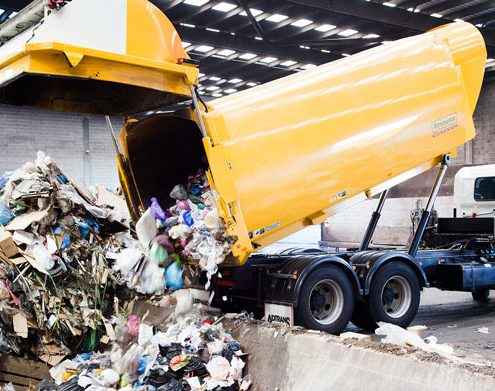 Garbage truck unloading solid waste